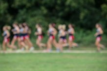 Female cross country team runners blurred in camera for effect