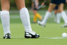 Legs of a field hockey player ready to inbound a ball.