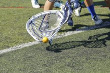 a lacrosse goalie scoops the ball from the ground